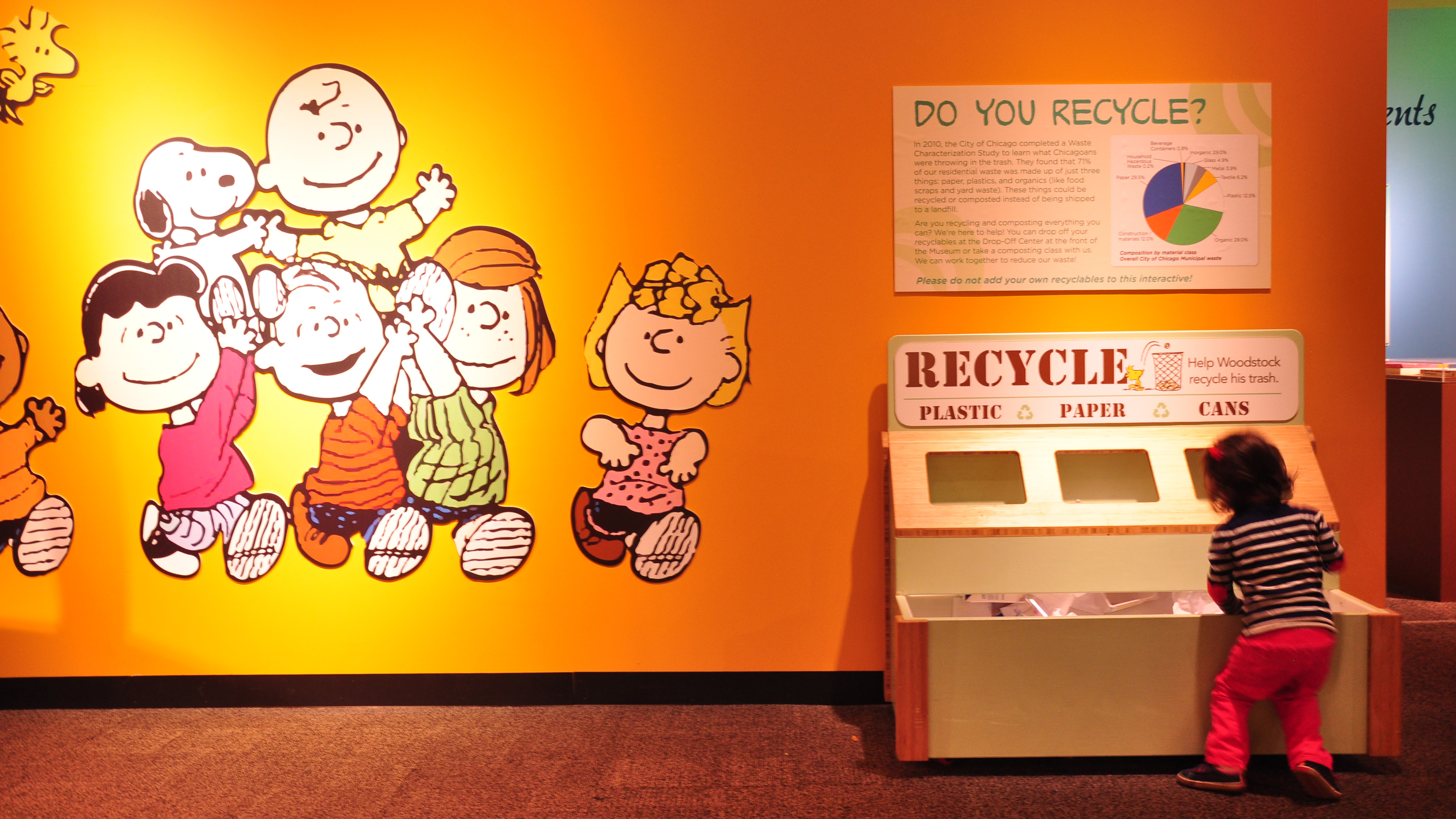 "A young visitor learns about recycling at the Nature Museum's ""Peanuts ... Naturally"" exhibit. (Sean Keenehan)"