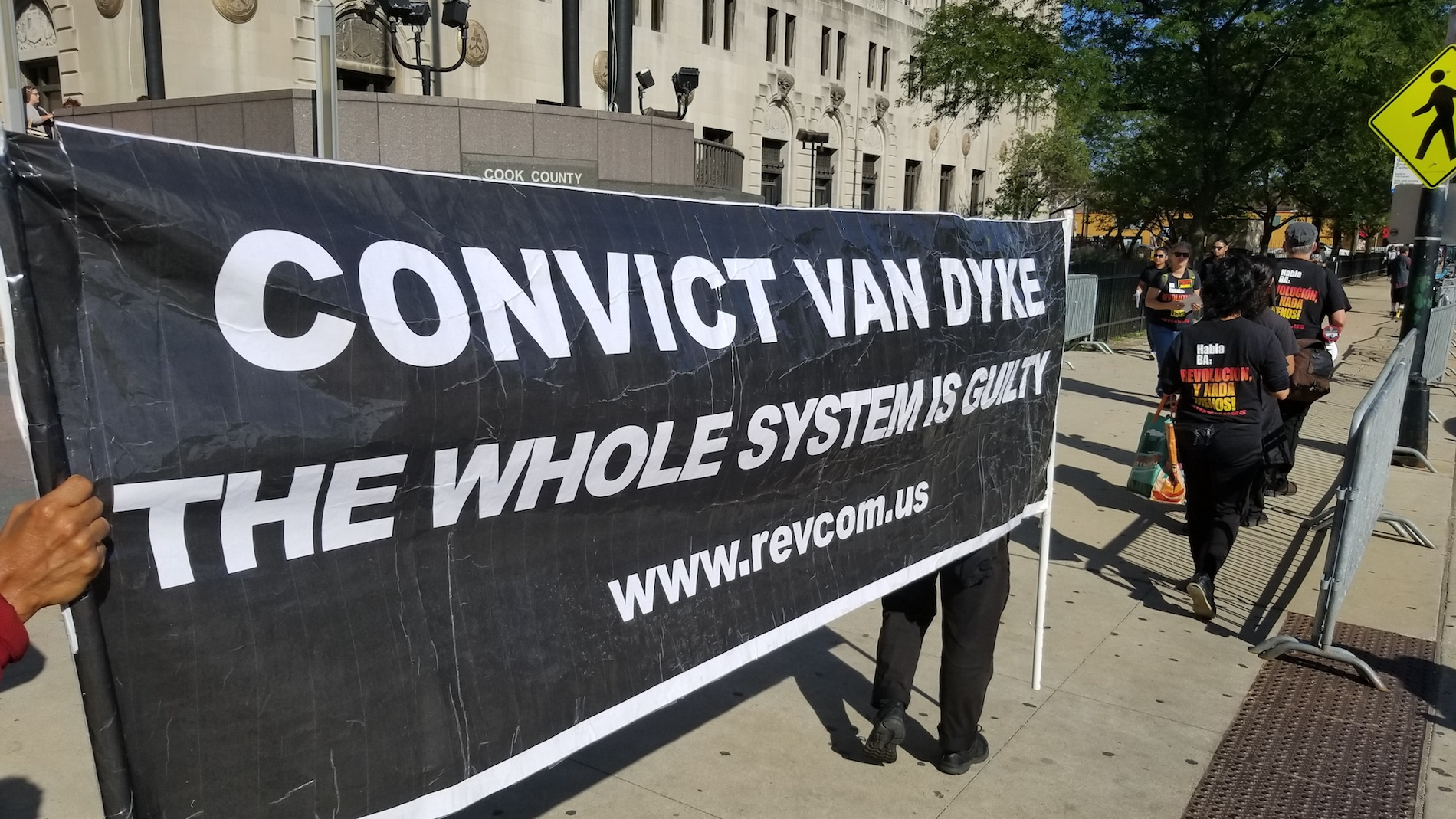 Protesters stand outside the Leighton Criminal Court building Monday, Sept. 10, 2018, the first day of jury selection in Jason Van Dyke's murder trial. (Matt Masterson / Chicago Tonight)