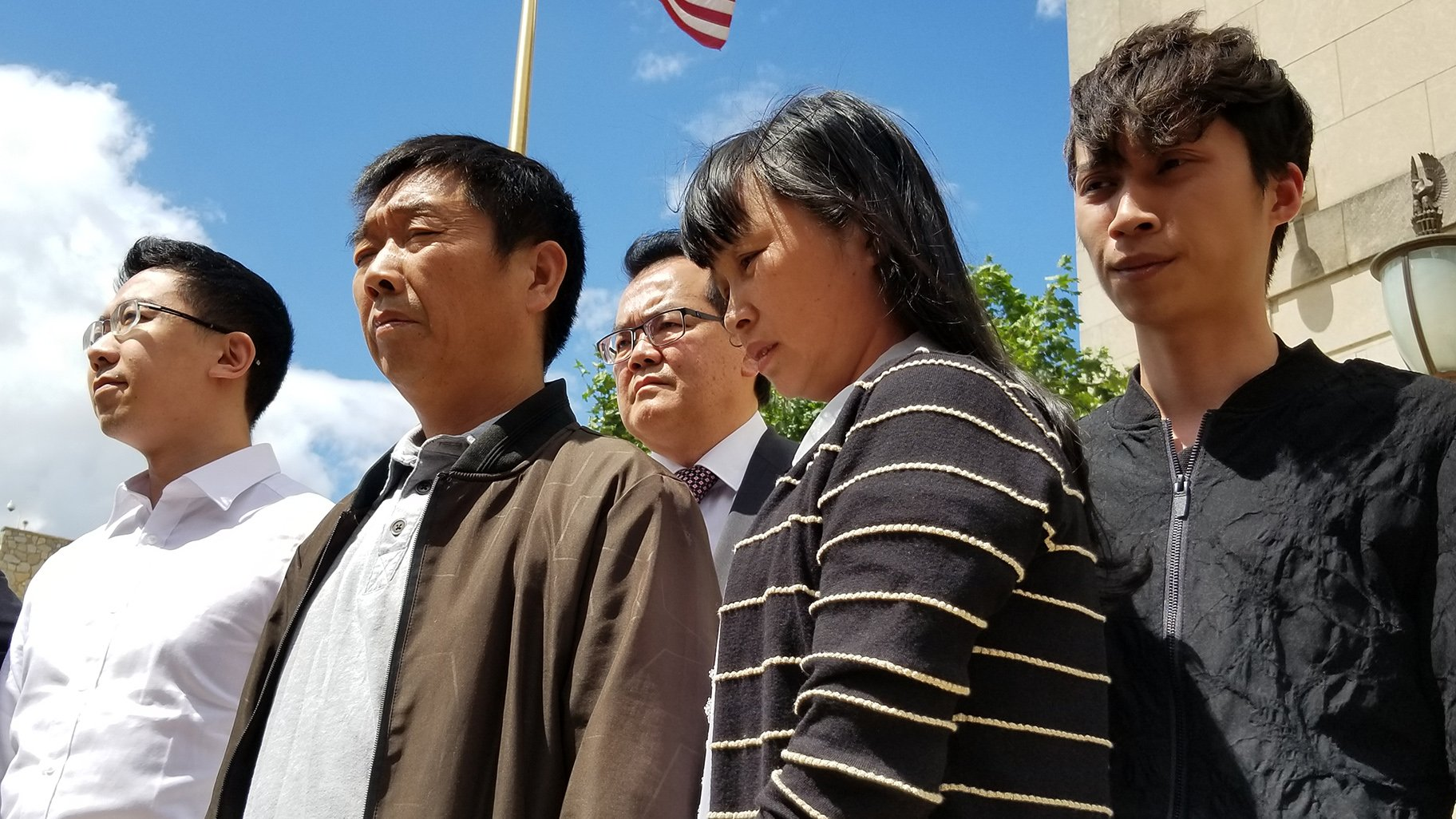 From left to right: Xiaolin Hou, Ronggao Zhang, Lifeng Ye and  Zhengyang Zhang stand outside the Peoria federal court building on June 24, 2019. (Matt Masterson / WTTW News)