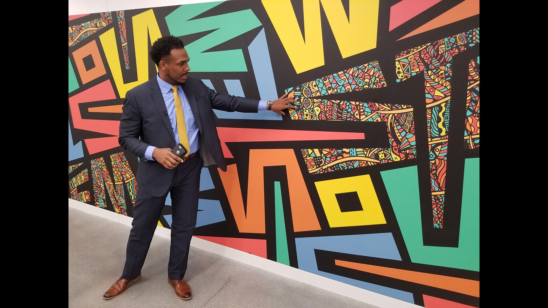 Englewood STEM Principal Conrad Timbers-Ausar shows off one of the murals inside his school's building. (Matt Masterson / WTTW News)