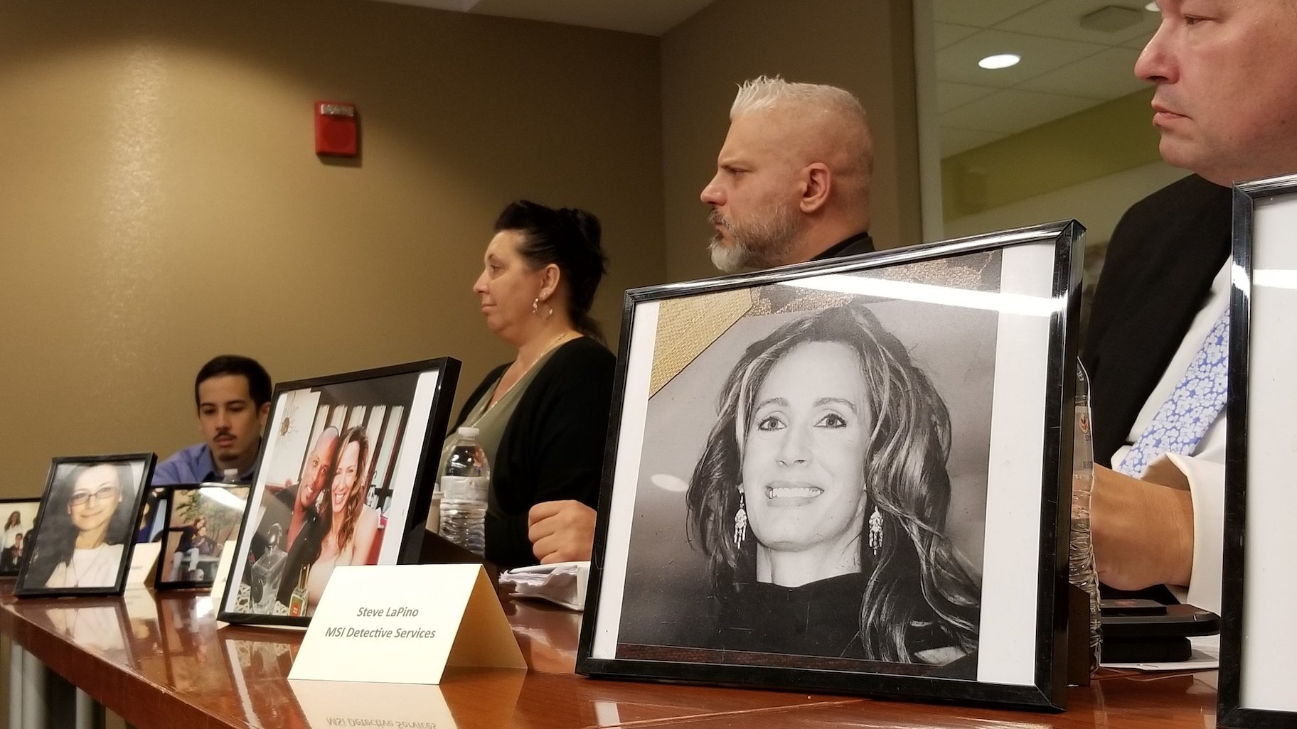 Members of Marni Yang's family and investigative team sit behind photos of Rhoni Reuter, who Yang was convicted of killing in 2007. (Matt Masterson / WTTW News)