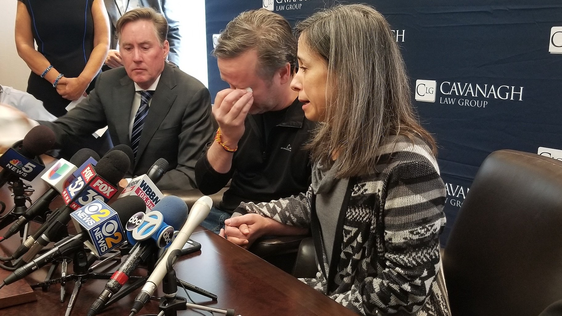 Tom Wilder, center, and Lucia Morales, right, say they're unsure if their son Rylan will ever regain full use of his arm after he was shot last week in an incident involving bank robbers and police. (Matt Masterson / WTTW News)