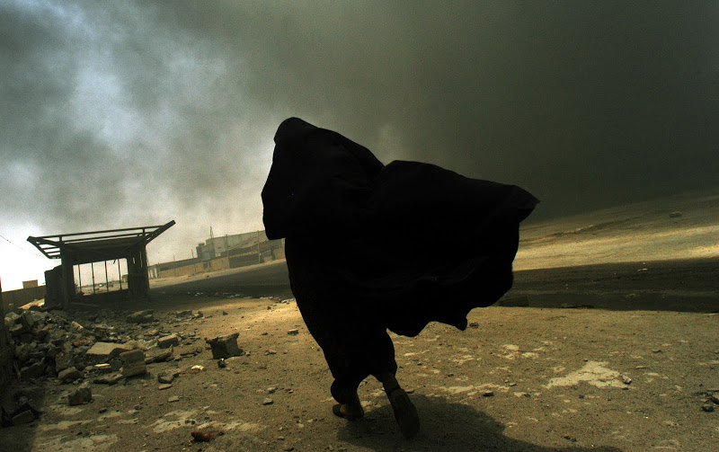 An Iraqi woman walks through a plume of smoke rising from a massive fire as she searches for her husband in Basra, Iraq, May 26, 2003. (Lynsey Addario / Corbis Saba)