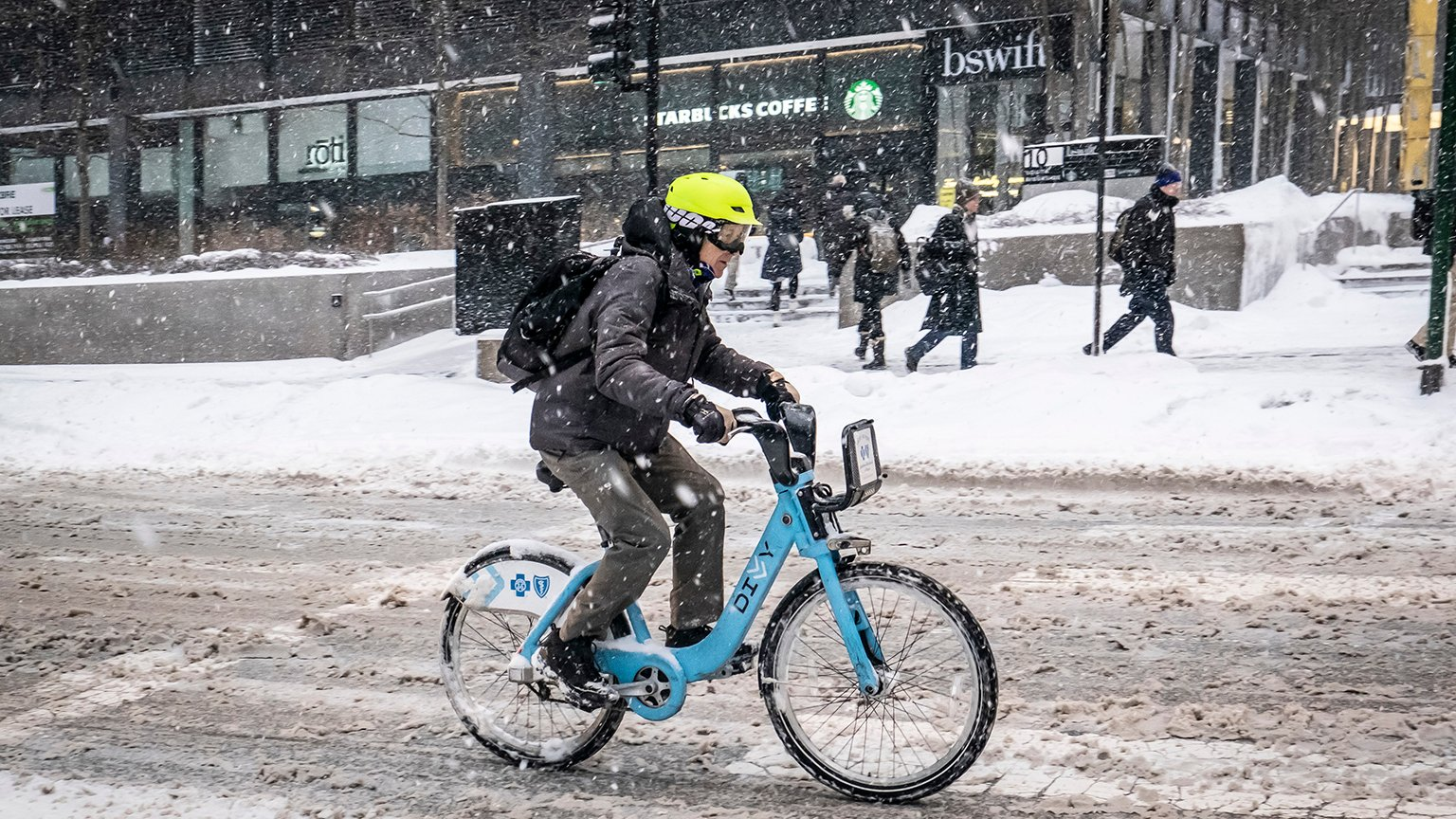 A person navigates a snowy Adams Street on a Divvy bicycle on Monday, Jan. 28, 2019. (Rich Hein / Chicago Sun-Times via AP)