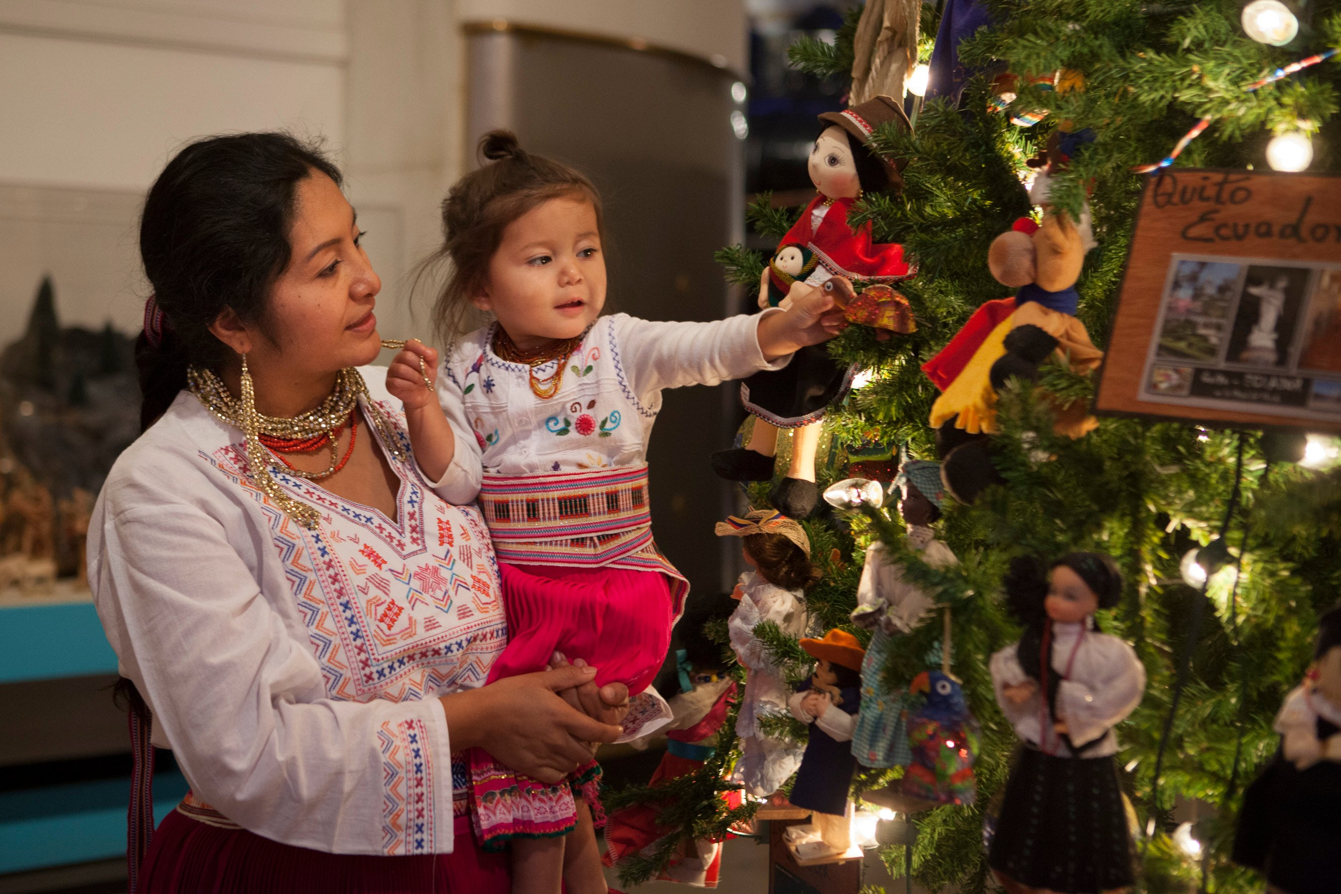 Volunteers, dressed in traditional Ecuadorian clothing, decorate the tree of Ecuador. (J.B. Spector, Museum of Science and Industry)