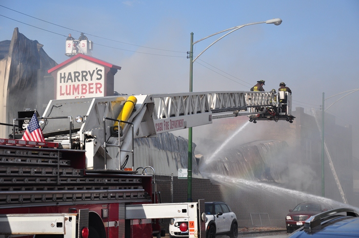 A rainbow appears through dark clouds of smoke as firefighters work to extinguish a 3-alarm fire at Harry's Lumber Company (Sean Keenehan)
