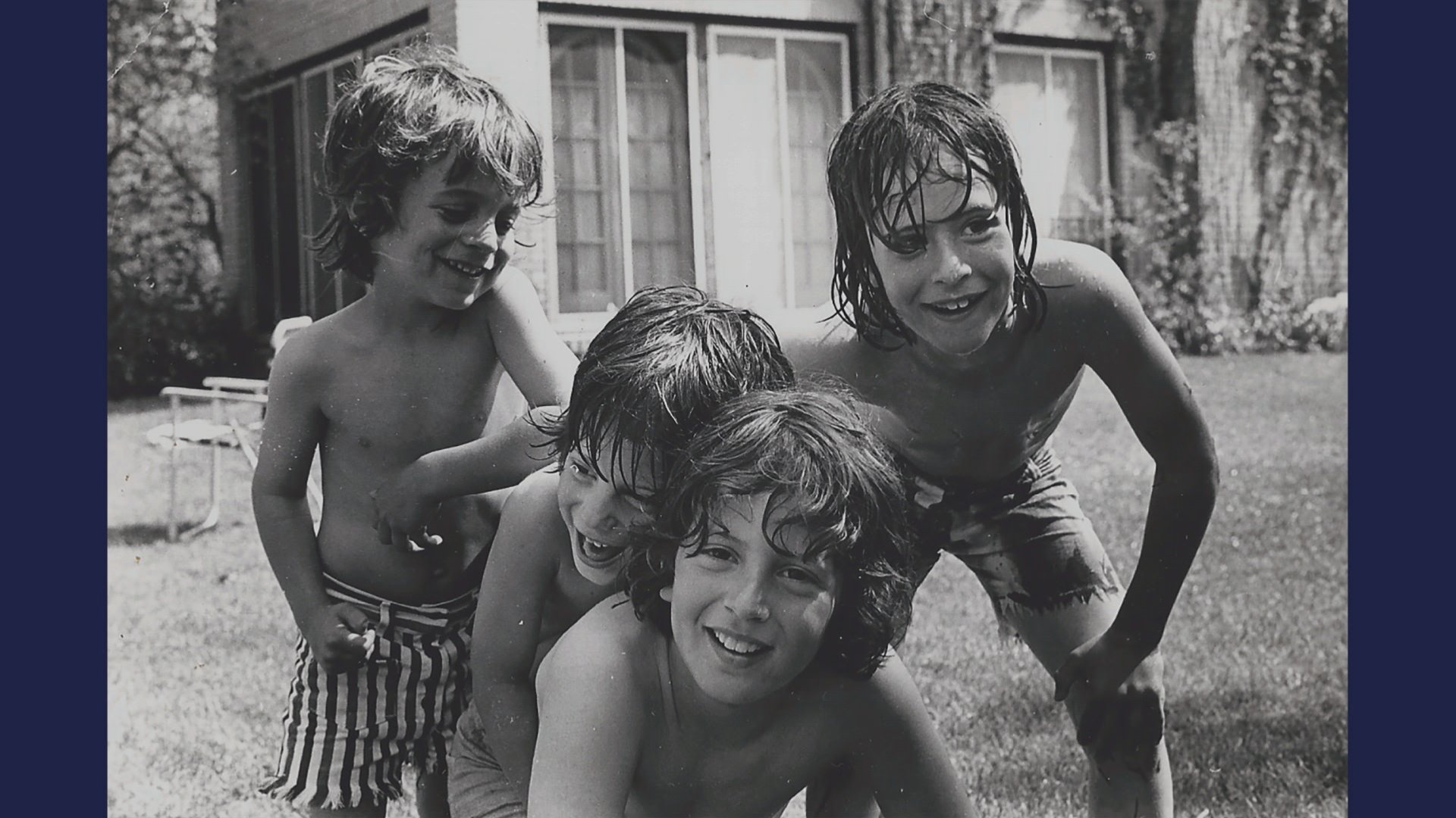 Adam and David Rudman, along with their two brothers, play in the backyard of their family home as kids.