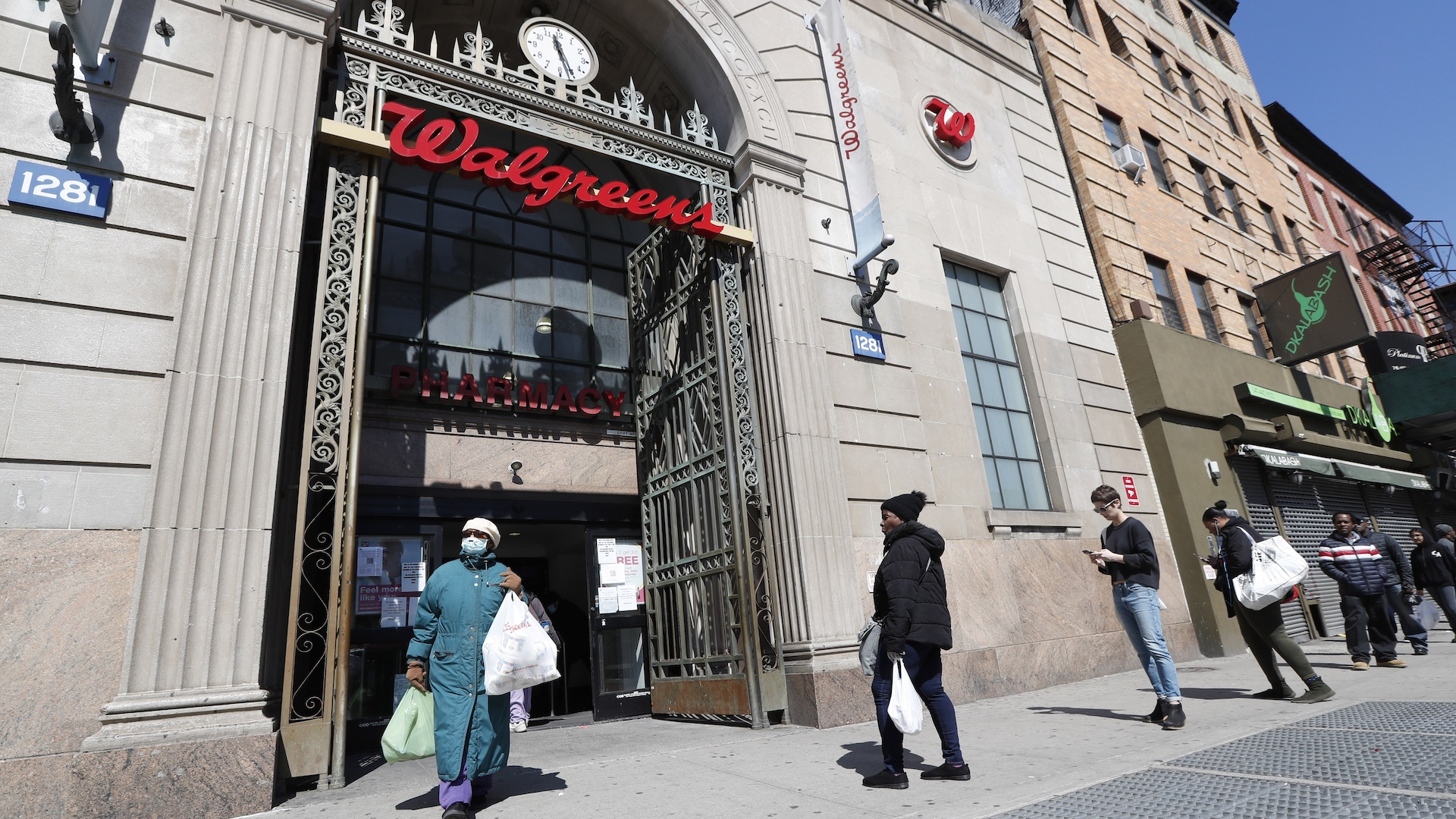 In this March 26, 2020 file photo, a woman leaves a Walgreens pharmacy that is enforcing social distancing rules by allowing only a certain numbers of people in as customers line up on the sidewalk outside the store in New York. The coronavirus pandemic pushed the drugstore chain to a .7-billion loss in its fiscal third quarter, as customers stayed home to avoid the virus or consolidated their shopping to grocery stores. (AP Photo/Kathy Willens, File)