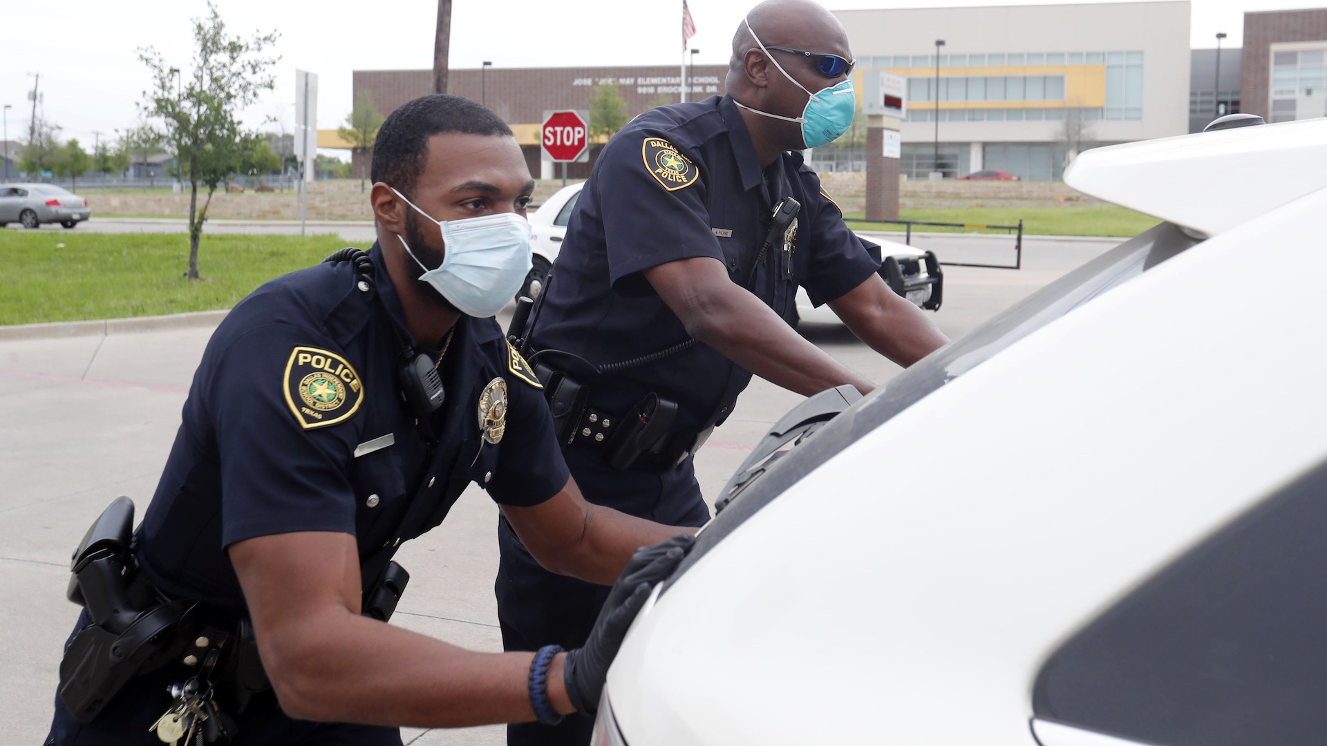 In this April 9, 2020, photo, amid concerns of the spread of COVID-19, Dallas ISD police officers Mylon Taylor, left, and Gary Pierre push a car that ran out of gas while waiting in line for the weekly school meal pick up for students in Dallas. The coronavirus pandemic that has crippled big-box retailers and mom and pop shops worldwide may be making a dent in illicit business, too. (AP Photo/LM Otero)