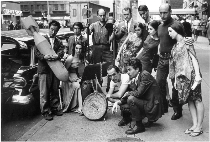 Publicity photograph for 3rd Annual New York Avant-Garde Festival, August 26, 1965. Left to right: Nam June Paik, Charlotte Moorman, Takehisa Kosugi, Gary Harris, Dick Higgins, Judith Kuemmerle, Kenneth King, Meredith Monk, Al Kurchin, Phoebe Neville. In front, kneeling, Philip Corner and James Tenney. (Photo, Peter Moore. Photograph © Barbara Moore/Licensed by VAGA, NY)