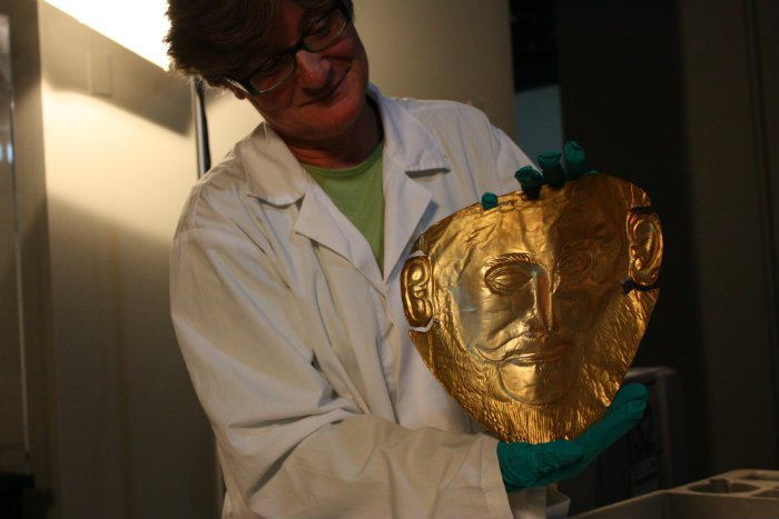 Angeliki Kossyva, an archeologist at the Museum of Mycenae, holds up a reproduction of the Mask of Agamemnon (Chloe Riley)