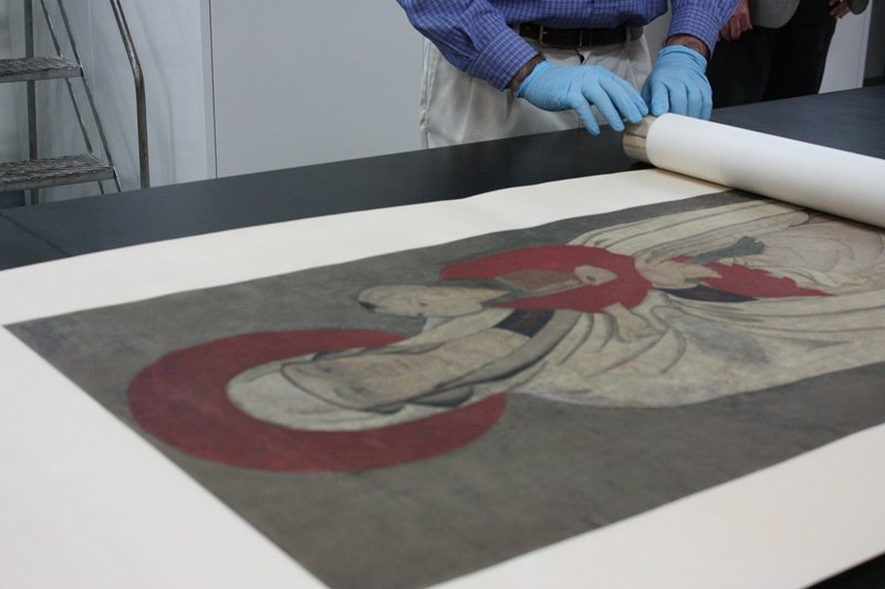 Unrolling of the Field Museum's Chinese Madonna scroll (Chloe Riley)