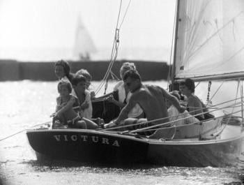 Robert F. Kennedy at the helm of <em>Victura</em>. Left to right: Maria Shriver, Courtney Kennedy, Bobby Shriver, Robert Kennedy Jr., Pat Prusyewski (a ward of the Shriver family), Robert F. Kennedy, David Kennedy, and Kathleen Kennedy. Photo courtesy of AP Photo/Bob Schutz, July 30 1961.