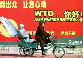 A Chinese couple on a tricycle pass a billboard welcoming the country's membership to the World Trade Organisation (WTO), along a street in Beijing, 23 December 2001. Image credit: AFP/Getty Images