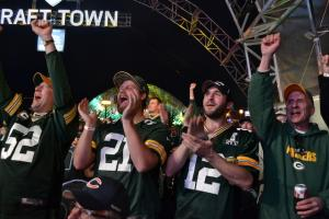 Green Bay Packers fans Travis Zaborski (second from right) and Matt Hiller (third from right) cheer on former Packers wide receiver Donald Driver announce the team's second round pick.