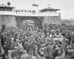 "Tanks of the US 11th Armored Division enter the Mauthausen concentration camp; banner in Spanish reads ""Antifascist Spaniards greet the forces of liberation"". The photo was taken on May 6, 1945"