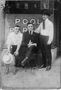 This is one of the earliest photographs of Al Capone. It was taken the day he graduated high school and before he had the scars on his face. He is sitting in front of the pool hall where his father, sitting next to Al, died of a massive heart attack in 1920. Look at the reflection in the window and you will see the apartment building across the street where they lived. The woman standing on the balcony is Al's mother Theresa holding my father who was just a month old. The man standing is Vincenzo Raiola. 1917.