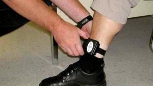 An individual being fitted with an electronic ankle bracelet. Courtesy of WORLD Law Direct.