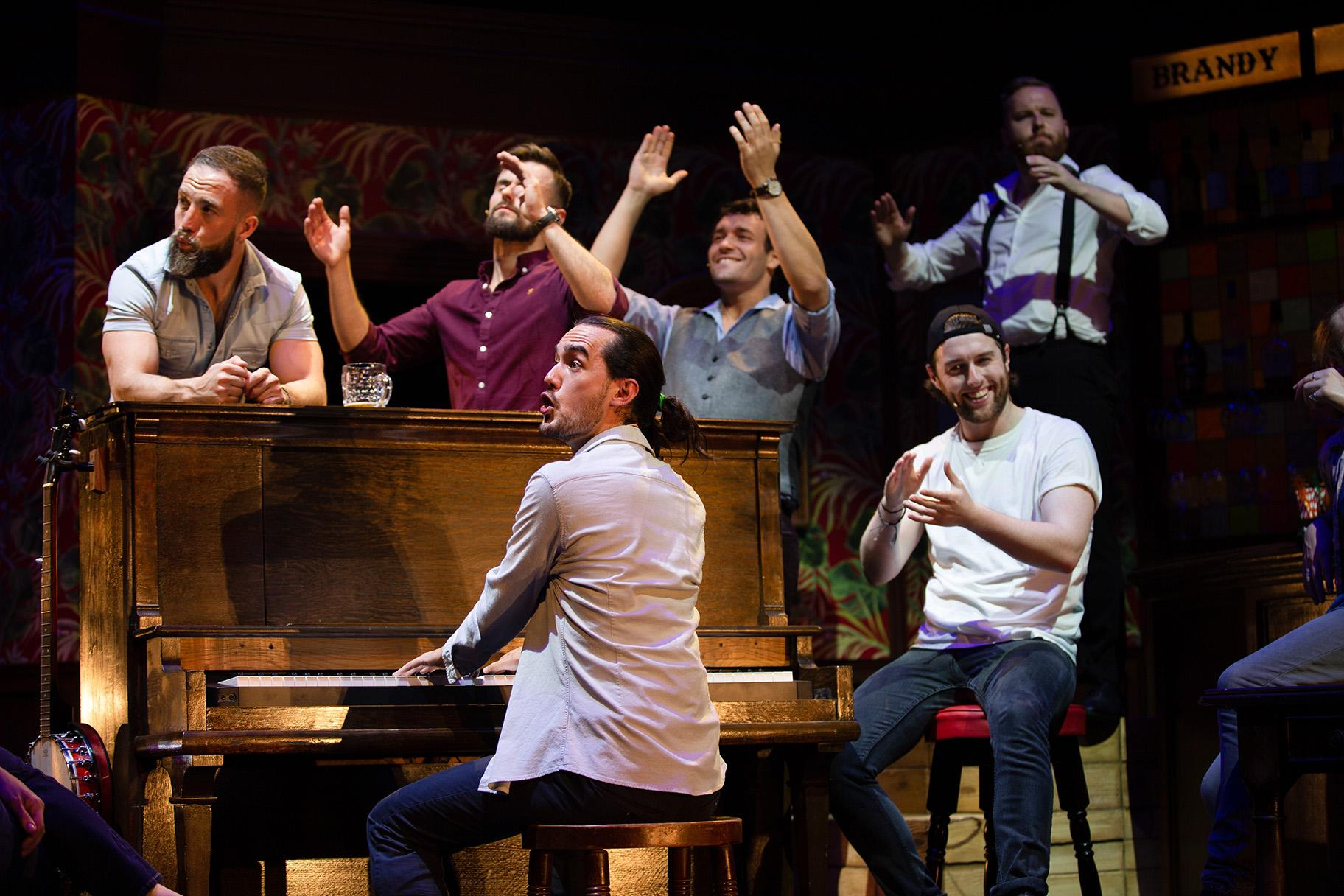 "From left: Tom Brandon, John Sheehy, Connor Going (at piano), Andrew Carter, Denis Grinden (seated) and Mark Loveday in ""The Choir of Man."" (Credit: Brian Wright)"