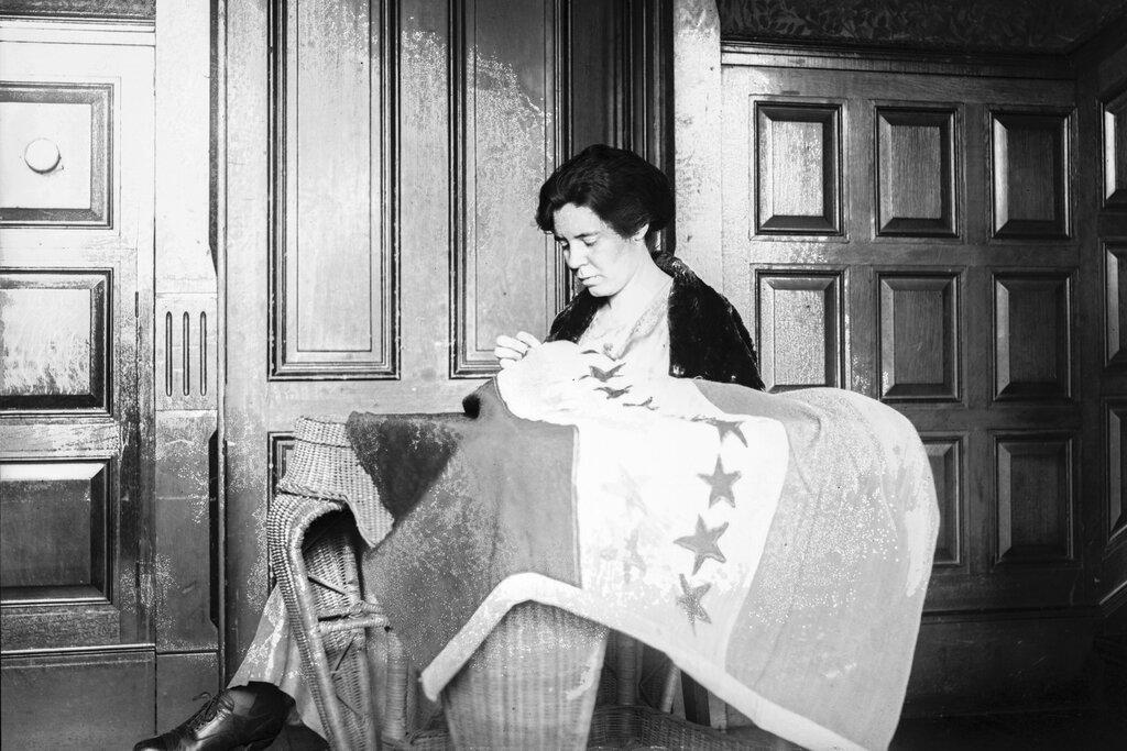 In this 1920s photo, Alice Paul sews a suffrage flag in Washington. One hundred years ago, American women gained the guaranteed right to vote, with ratification of the 19th Amendment. (National Photo Company Collection / Library of Congress via AP)