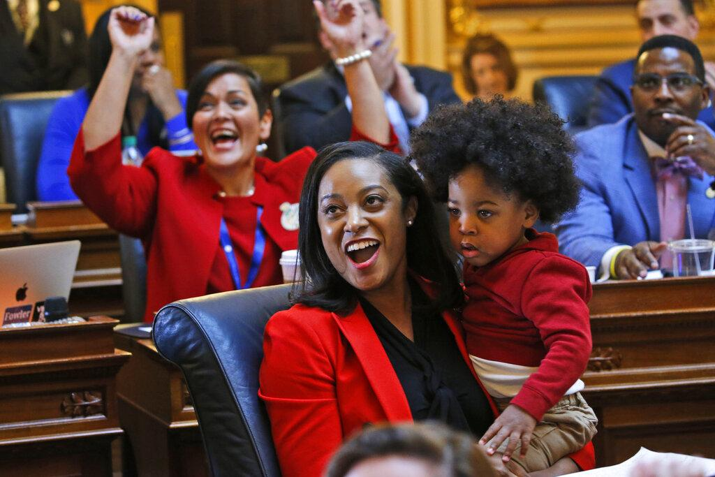 In this Jan 27, 2020, file photo, Virginia Delegate Jennifer Carroll Foy holds her son, Alex Foy, as she and Delegate Hala Ayala, D-Prince William, back, celebrate the passage of the Equal Rights Amendment in the House chambers at the Capitol in Richmond, Va. (AP Photo / Steve Helber, File)