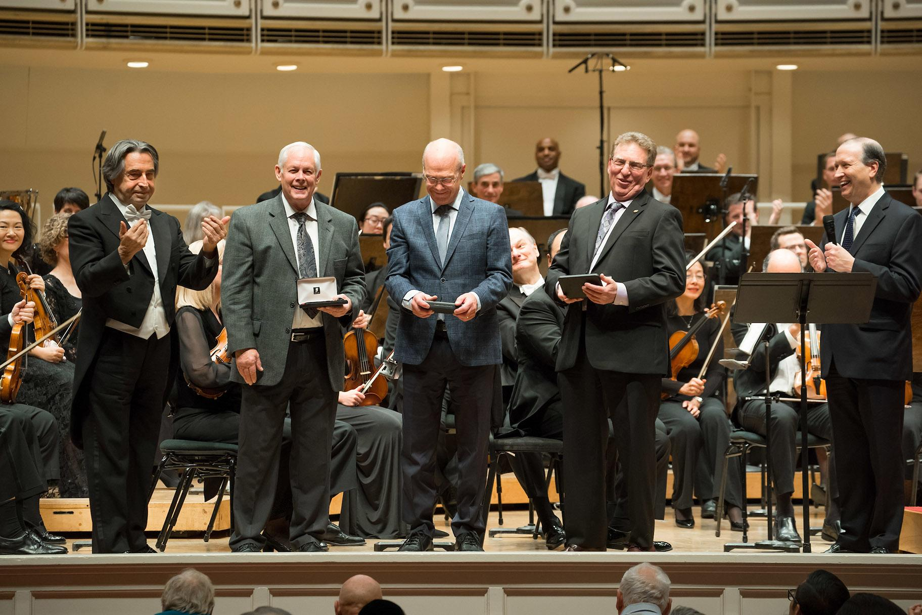 Zell Music Director Riccardo Muti (left) and Chicago Symphony Orchestra President Jeff Alexander (far right) present Theodore Thomas Medallions to recognize retiring musicians of the CSO, Roger Cline, bass, John Bartholomew, viola, and Daniel Orbach, viola at Symphony Center on Nov. 7, 2019. (Credit: Anne Ryan)
