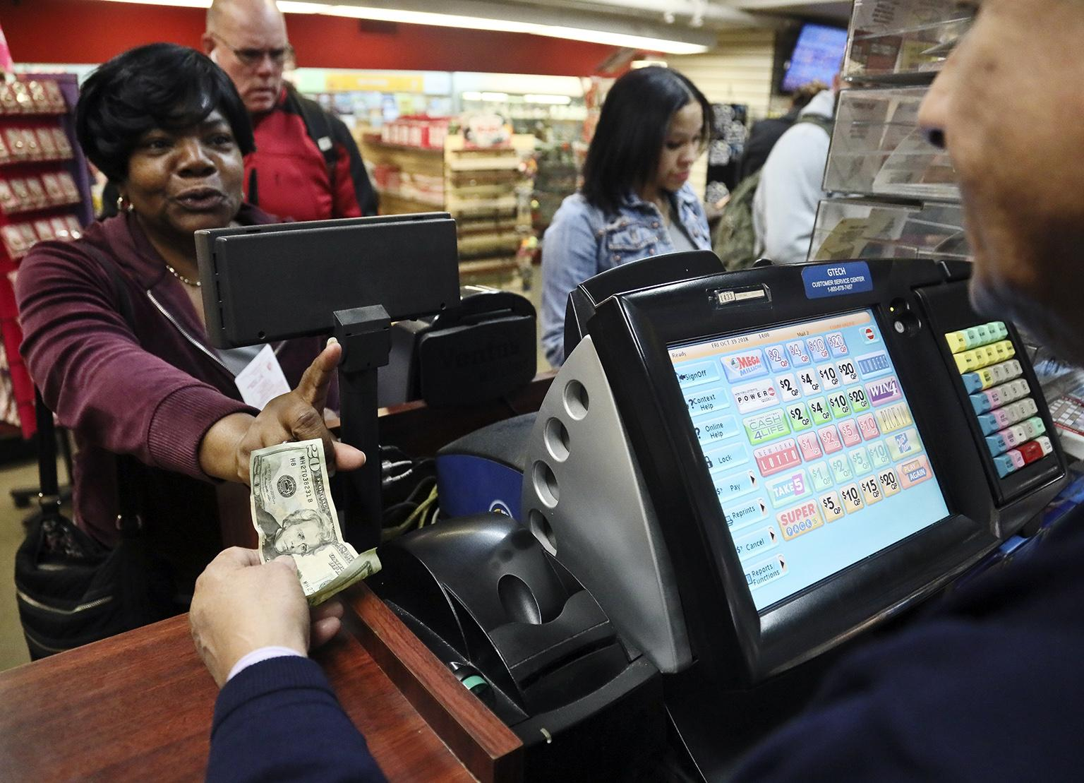 "Annette Gray, left, from Valley Stream, N.Y., buys lottery tickets on Friday, Oct. 19, 2018, in New York. The estimated jackpot for Friday's Mega Millions drawing has soared to  billion. Gray said it's about ""a dollar and a dream, but I spent ten today."" (AP Photo / Bebeto Matthews)"