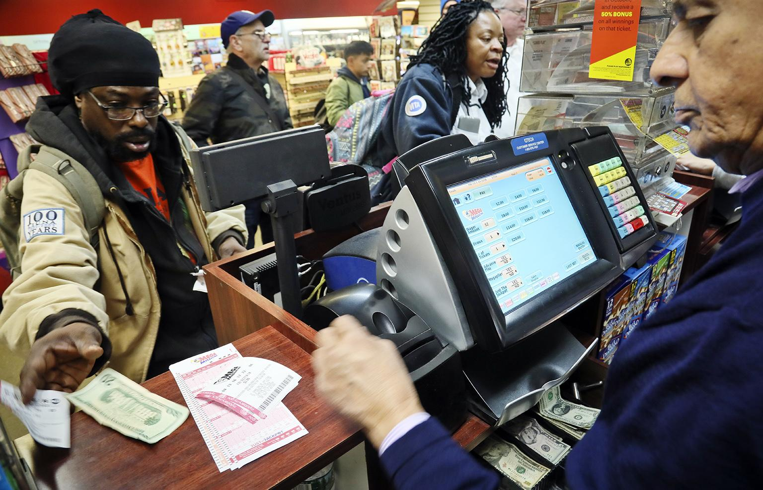 Lottery players buy Mega Millions lottery tickets on Friday, Oct. 19, 2018, in New York. The estimated jackpot for Friday's drawing has soared to  billion. (AP Photo / Bebeto Matthews)