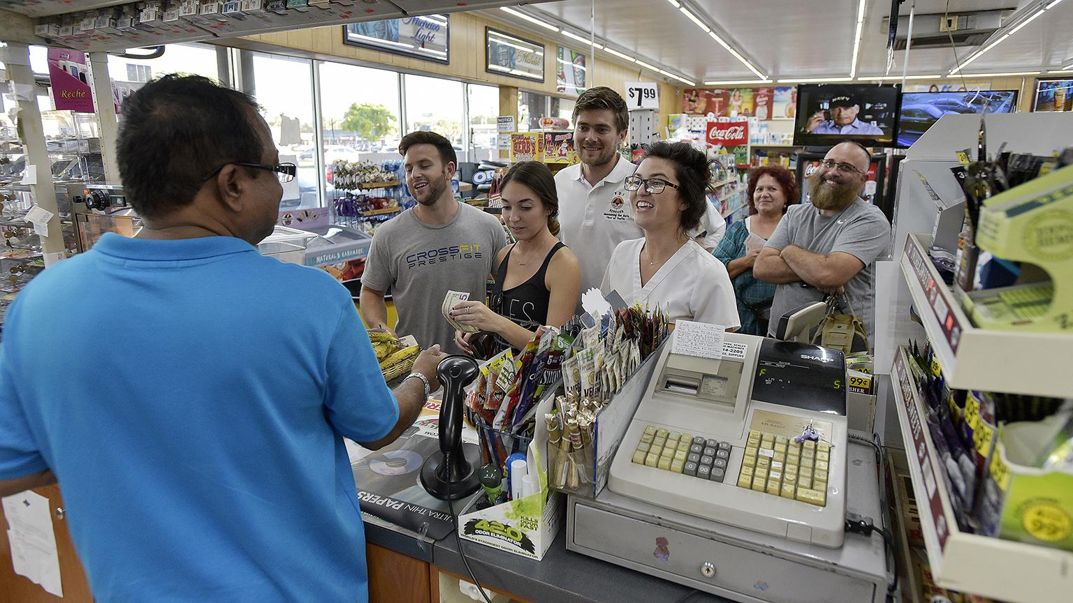 People line up at the Kwik Stop food store at 46th Avenue and Hollywood Boulevard, in Hollywood, Fla., to buy Mega Millions lottery tickets on Friday, Oct. 19, 2018.  (Michael Laughlin / South Florida Sun-Sentinel via AP)