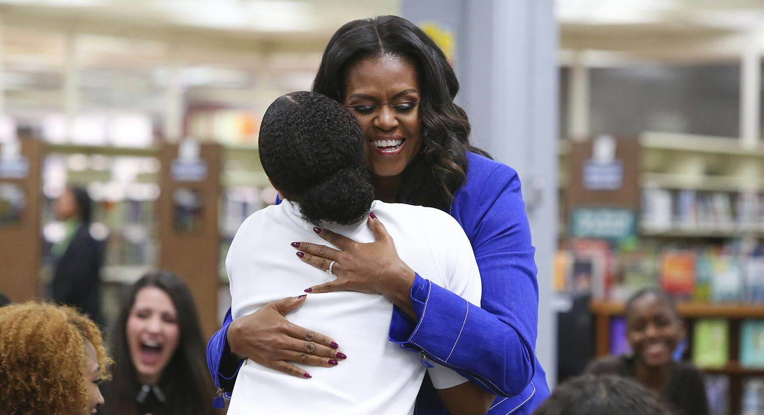 "Former first lady Michelle Obama embraces a student at her alma mater, Whitney M. Young Magnet High School, on Chicago's West Side, Monday, Nov. 12, 2018, a day before the launch of a book tour to promote her memoir, ""Becoming."" (AP Photo / Teresa Crawford)"