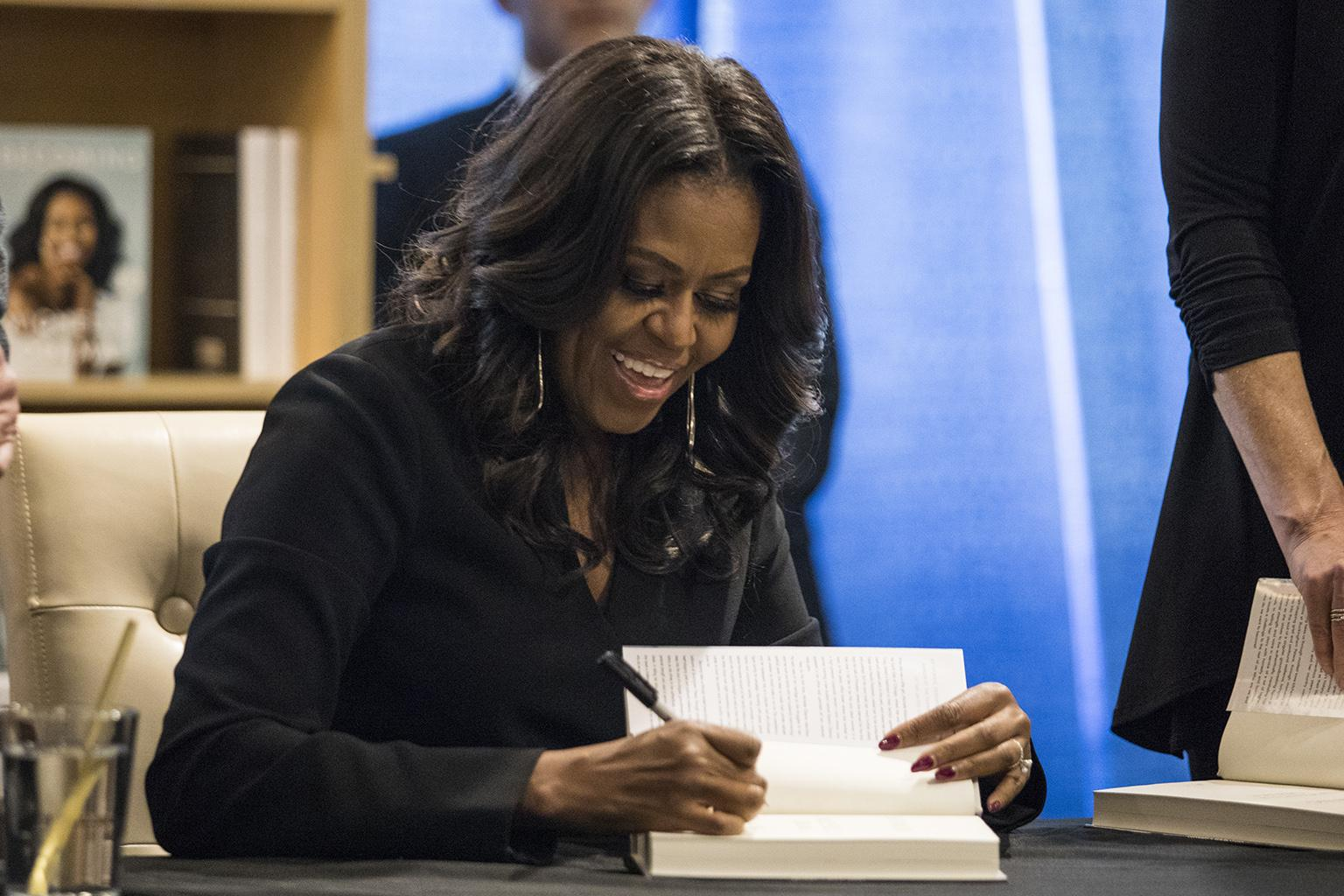 "Former first lady Michelle Obama signs copies of her new book ""Becoming"" and greets fans as she kicks off a national book tour at Seminary Co-op Bookstore in Chicago, Tuesday, Nov. 13, 2018. (Ashlee Rezin / Chicago Sun-Times via AP)"