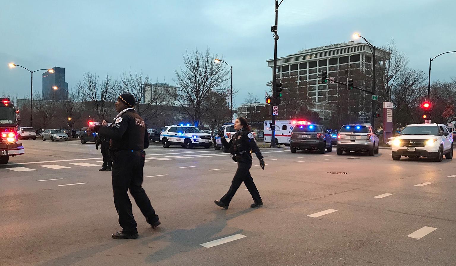 Chicago police officers walk outside Mercy Hospital on the city's Near South Side where authorities say a shooting at the hospital has wounded multiple people, including a suspect and a police officer on Monday, Nov. 19, 2018. (AP Photo / Amanda Seitz)