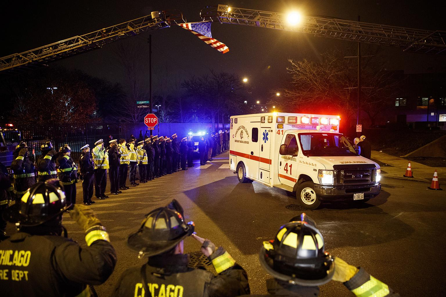 Police and firefighters salute as an ambulance arrives at the medical examiner's office carrying the body of Chicago Police Department Officer Samuel Jimenez, who was killed during a shooting at Mercy Hospital earlier in the day, Monday, Nov. 19, 2018. (Armando L. Sanchez / Chicago Tribune via AP)