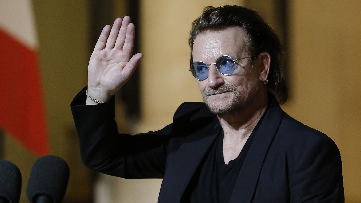 In this Monday, Sept. 10, 2018, file photo, U2 singer Bono waves goodbye to the media after a meeting with French President Emmanuel Macron at the Elysee Palace in Paris, France. (Michel Euler / AP File Photo)