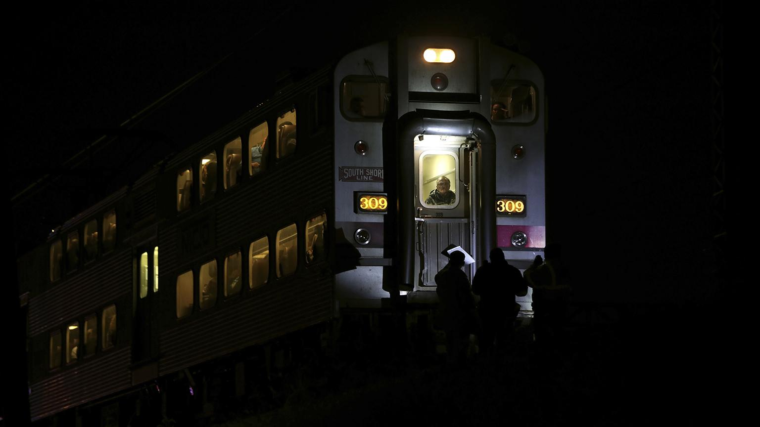Passengers sit on a train while police officers work the scene where two officers were killed after they were struck Monday, Dec. 17, 2018 by a South Shore train near 103rd Street and Dauphin Avenue. (E. Jason Wambsgans / Chicago Tribune via AP)