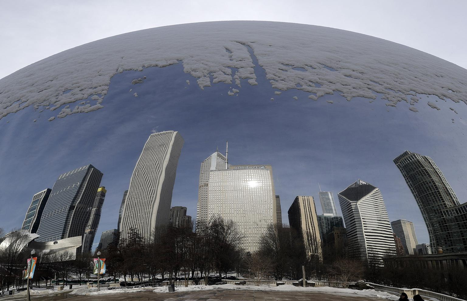 "Reflections of a snowy city are seen in the 110-ton stainless steel Anish Kapoor sculpture called ""Cloud Gate"" at Millennium Park in Chicago, Sunday, Jan. 27, 2019. (AP Photo / Nam Y. Huh)"