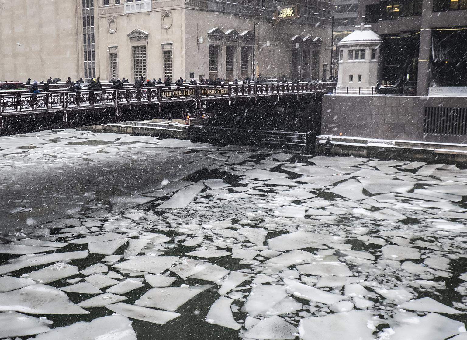 Pedestrians cross an icy Chicago River on Madison Street near the Civic Opera House on Monday, Jan. 28, 2019. (Rich Hein / Chicago Sun-Times via AP)