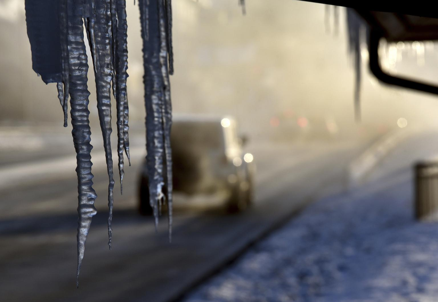 Icicles hang from the Harrington Inn in Geneva, Ill., as commuters pass by on Thursday, Jan. 31, 2019. (Jeff Knox / Daily Herald via AP)