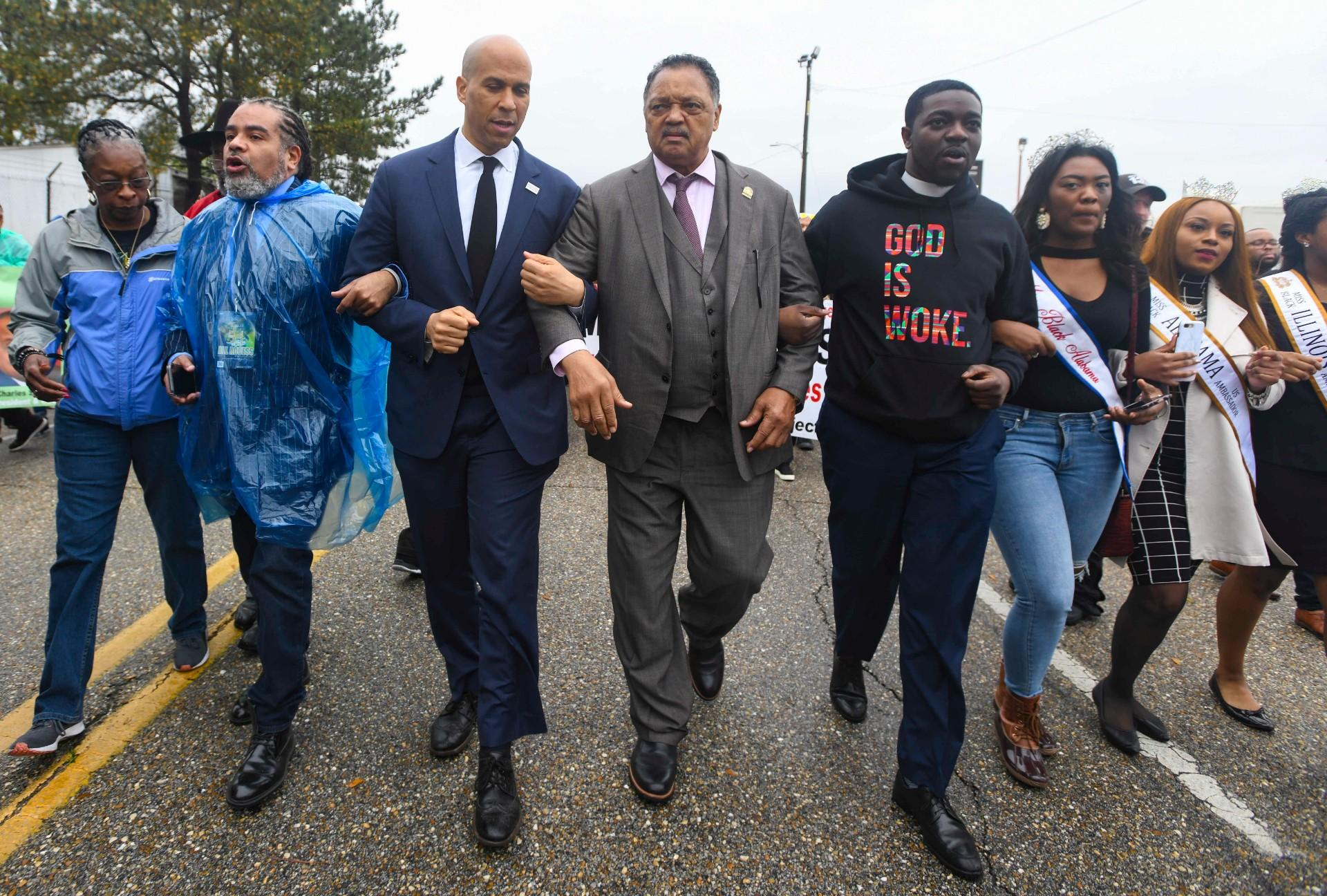"U.S. Sen. Cory Booker, D-N.J., third from left, and the Rev. Jesse Jackson march to cross the Edmund Pettus Bridge Sunday, March 3, 2019, during the Bloody Sunday commemoration in Selma, Ala. The infamous ""Bloody Sunday"" on March 7, 1965, galvanized support for the passage of the Voting Rights Act that year. (AP Photo / Julie Bennett)"
