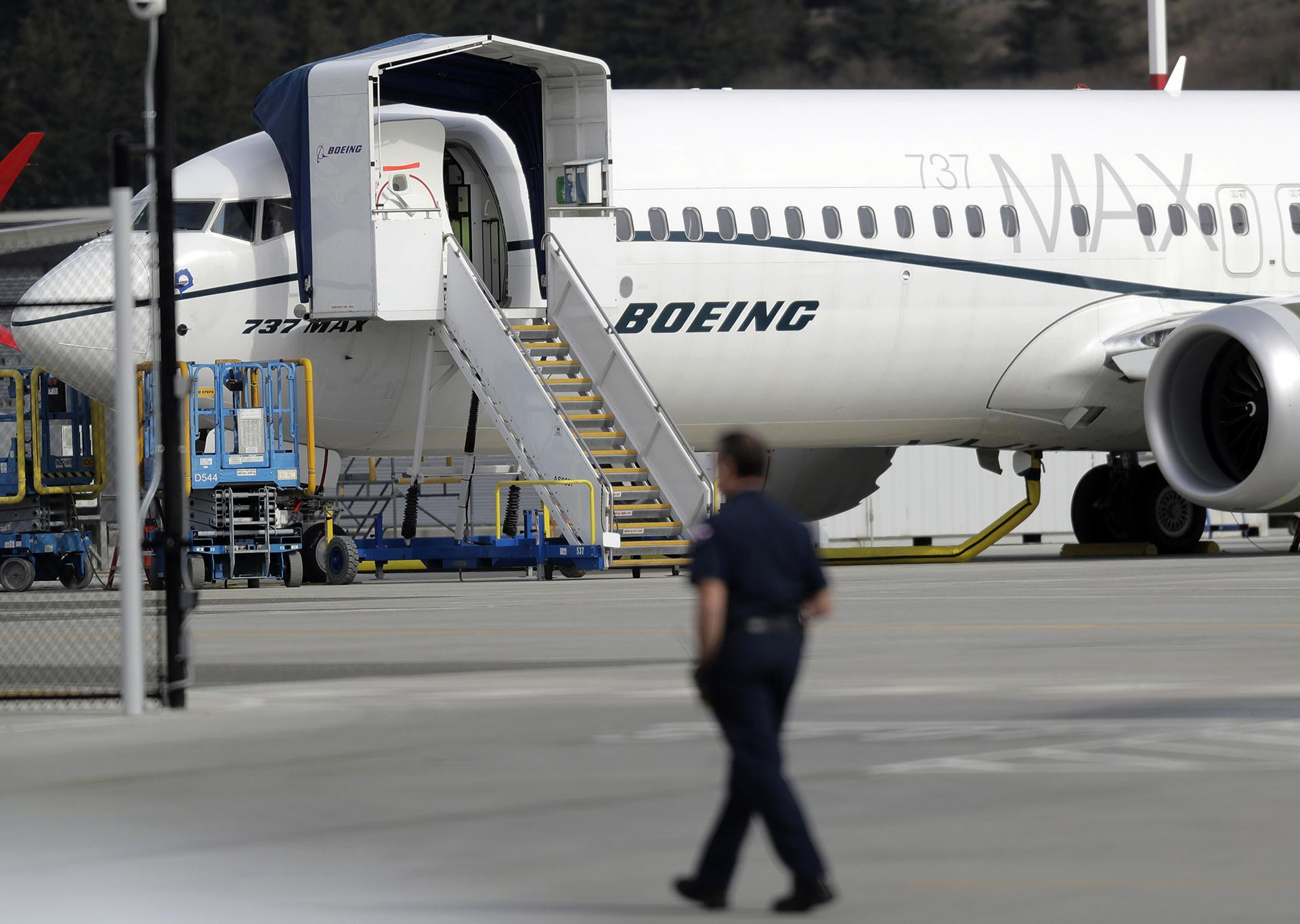 In this March 14, 2019, file photo a worker walks next to a Boeing 737 MAX 8 airplane parked at Boeing Field in Seattle. (AP Photo / Ted S. Warren, File)