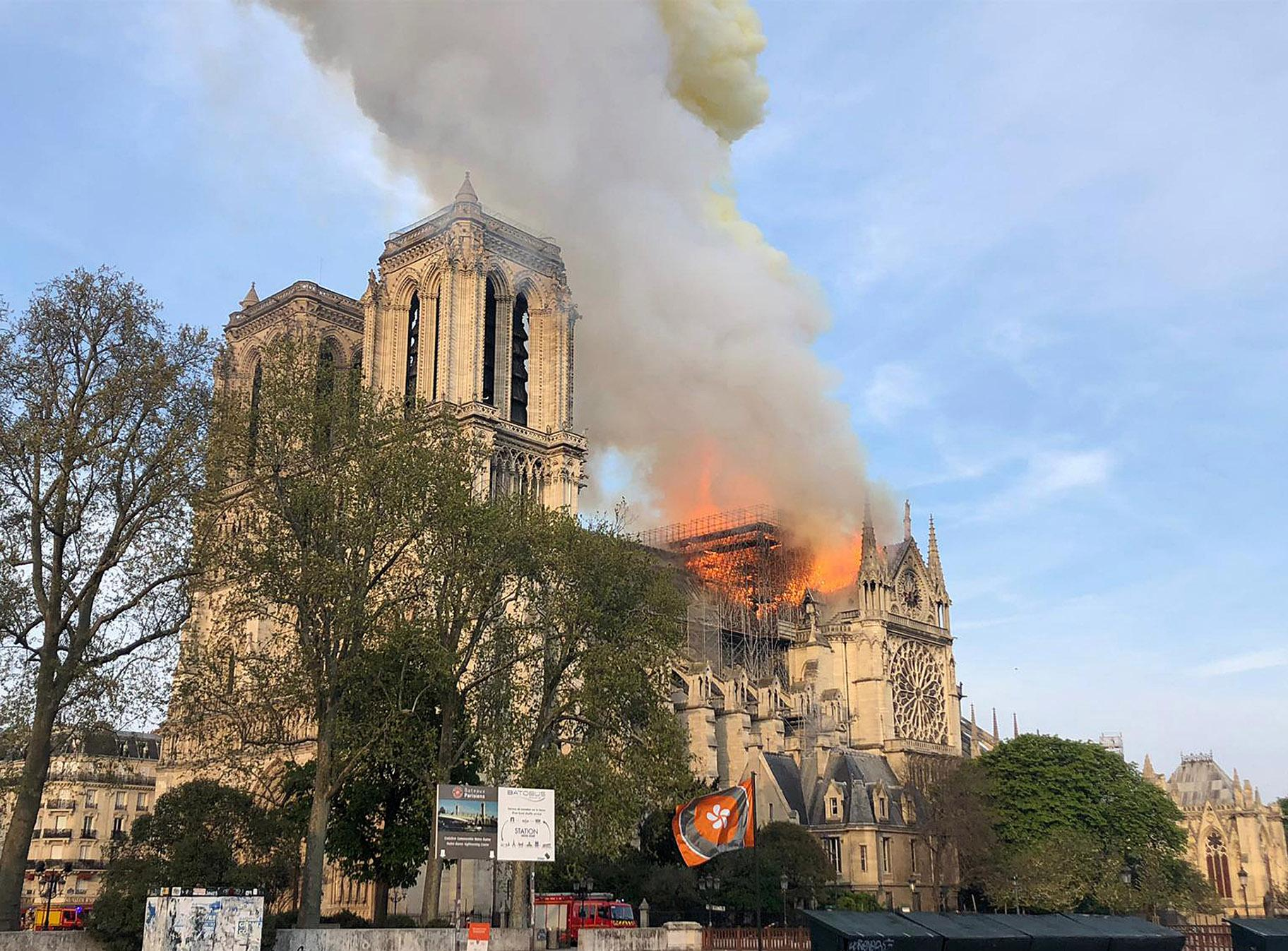 Notre Dame Cathedral is burning in Paris on Monday, April 15, 2019. Massive plumes of yellow brown smoke is filling the air above Notre Dame Cathedral and ash is falling on tourists and others around the island that marks the center of Paris. (AP Photo)