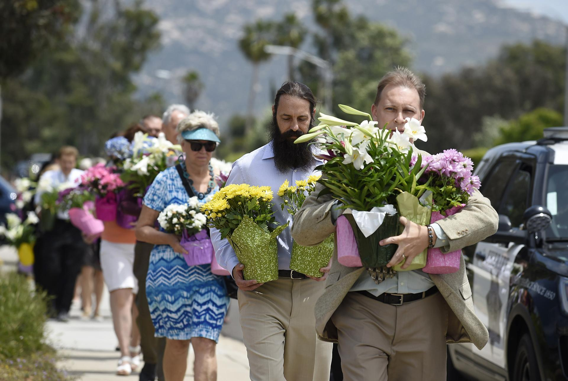 Members of the St. John of Damascus Orthodox Church bring flowers to a memorial at the Chabad of Poway synagogue, Sunday, April 28, 2019, in Poway, California. (AP Photo / Denis Poroy)