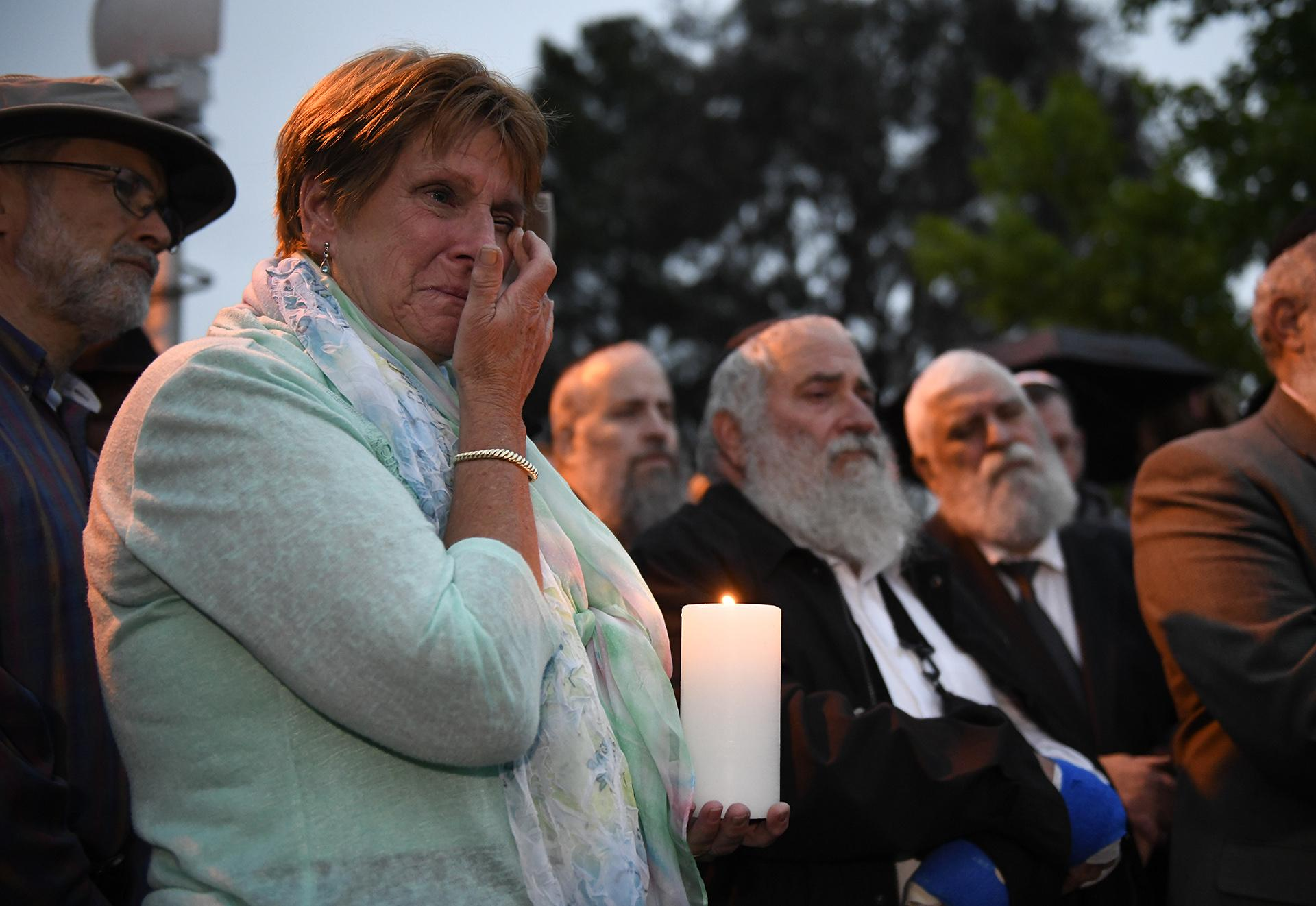 A woman cries during a candlelight vigil held for victims of the Chabad of Poway synagogue shooting, Sunday, April 28, 2019, in Poway, California. (AP Photo / Denis Poroy)