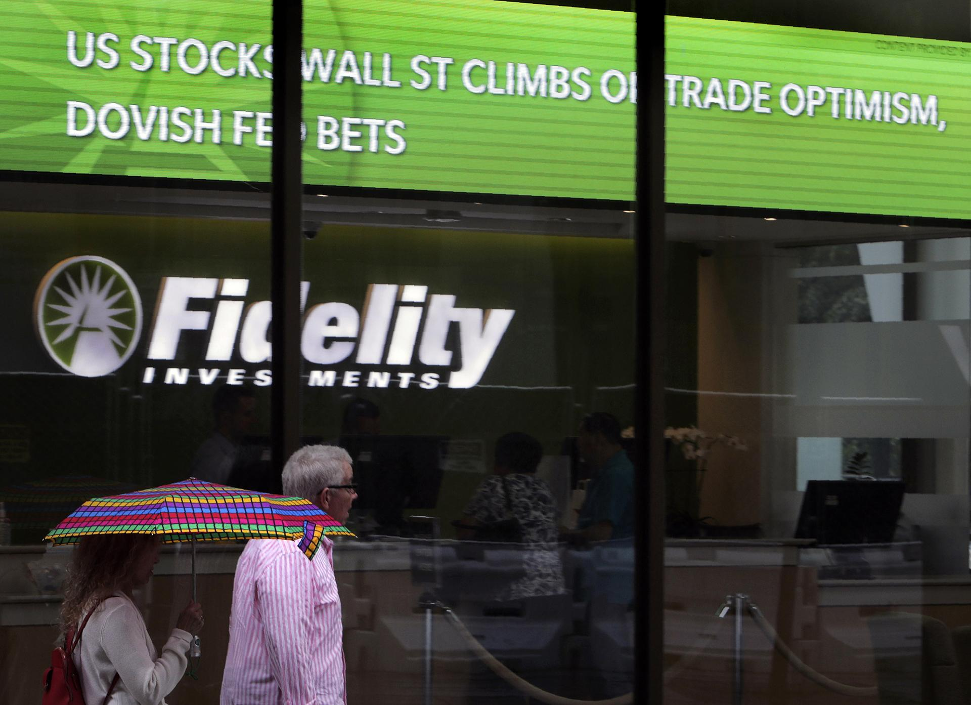 In this June 18, 2019, photo people walk past Fidelity Investments news scroll board, showing a favorable outlook in the US stock markets, in the Financial District of Boston. (AP Photo / Charles Krupa)