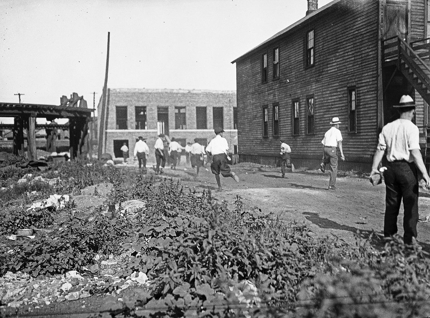 In this 1919 photo provided by the Chicago History Museum, a mob runs with bricks during the race riots in Chicago. (Chicago History Museum / The Jun Fujita negatives collection via AP)