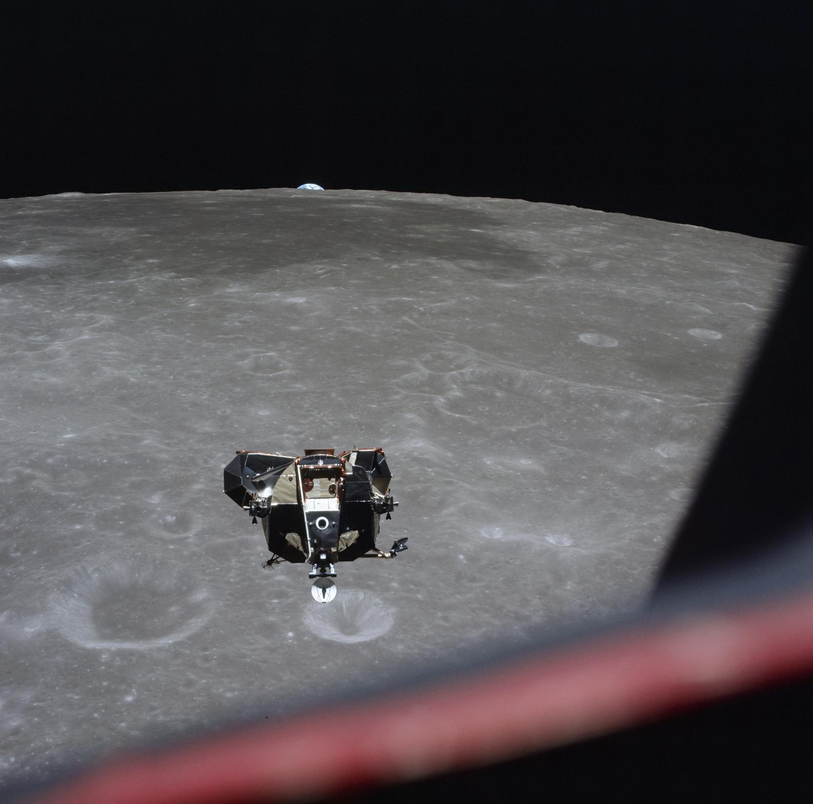 This July 21, 1969 photo made available by NASA shows the Lunar Module approaching the Command Module with the Earth visible behind the moon. (Michael Collins / NASA via AP)