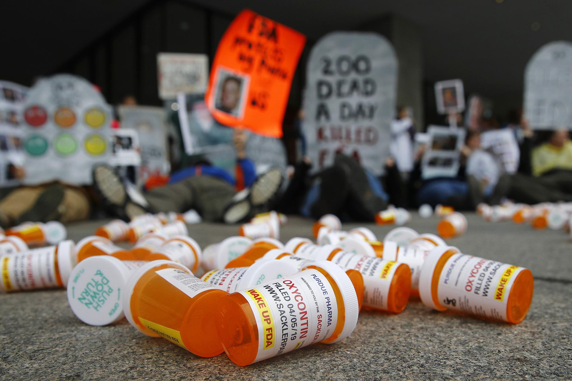 In this April 5, 2019, file photo, containers depicting OxyContin prescription pill bottles lie on the ground in front of the Department of Health and Human Services' headquarters in Washington as protesters demonstrate against the FDA's opioid prescription drug approval practices. (AP Photo / Patrick Semansky, File)