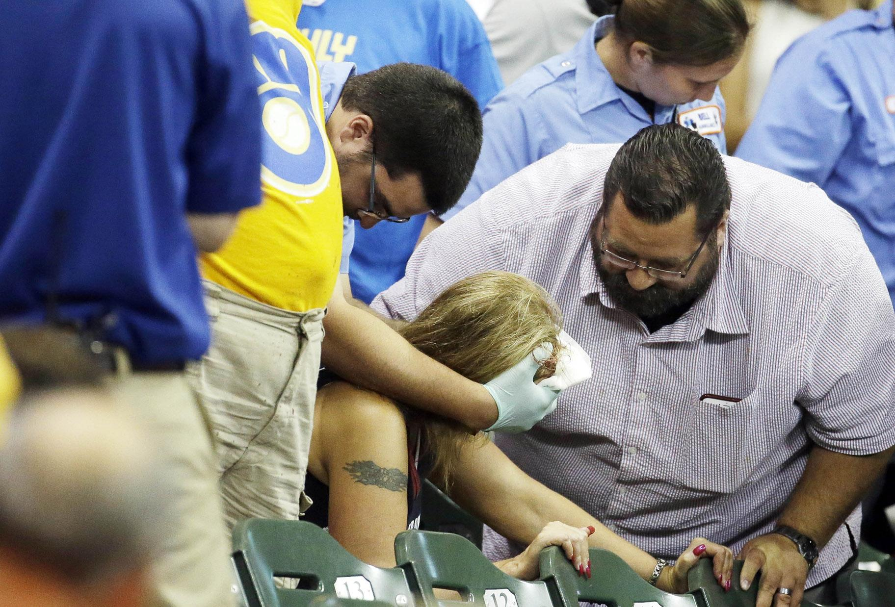 In this July 6, 2015 file photo, a fan is helped after being hit by a foul ball during the ninth inning of a baseball game between the Milwaukee Brewers and the Atlanta Braves in Milwaukee. (AP Photo / Morry Gash, File)