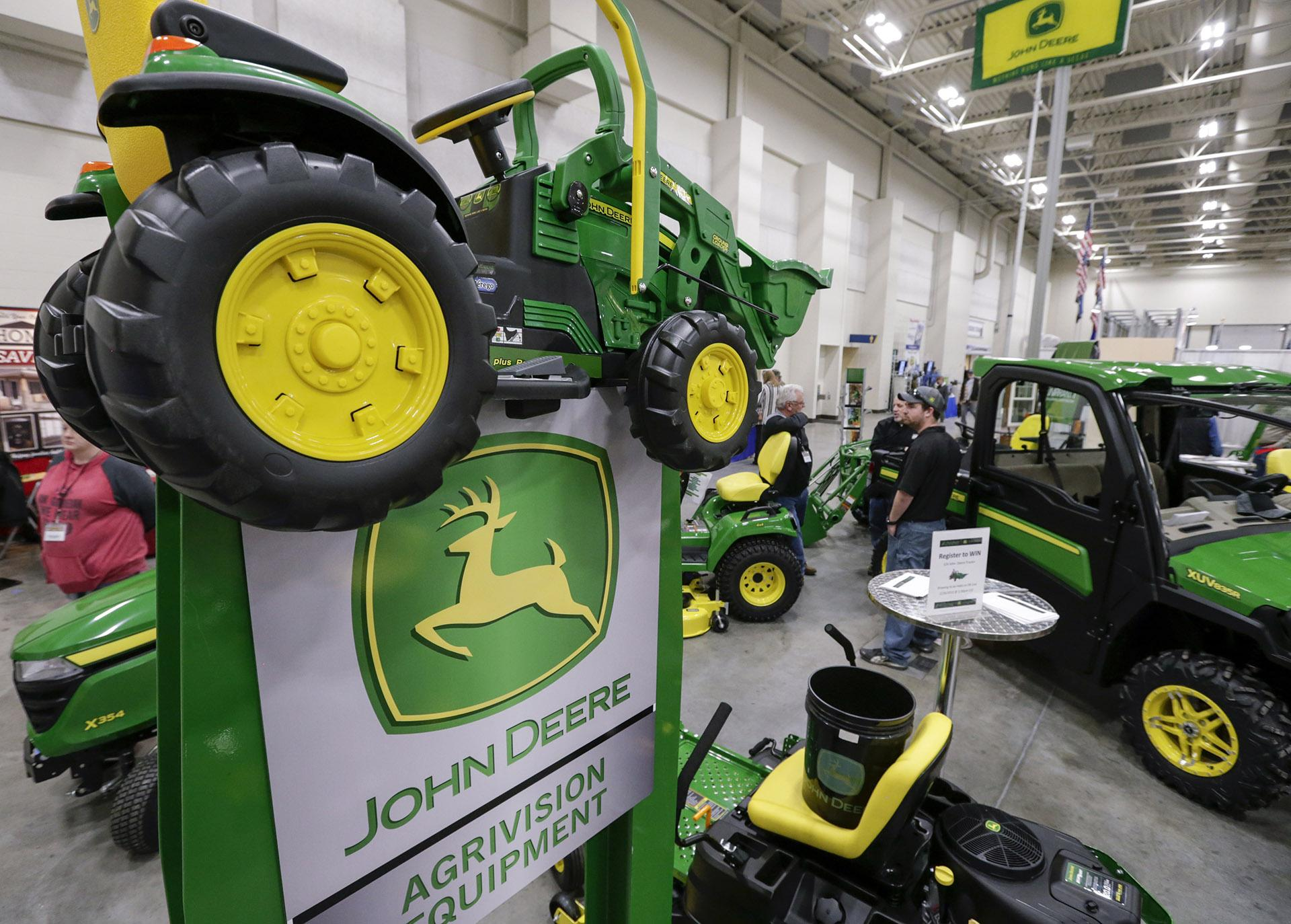 In this Feb. 23, 2018 file photo, John Deere products, including a toy tractor on the sign, are on display at a home and garden trade show in Council Bluffs, Iowa. (AP Photo / Nati Harnik, File)