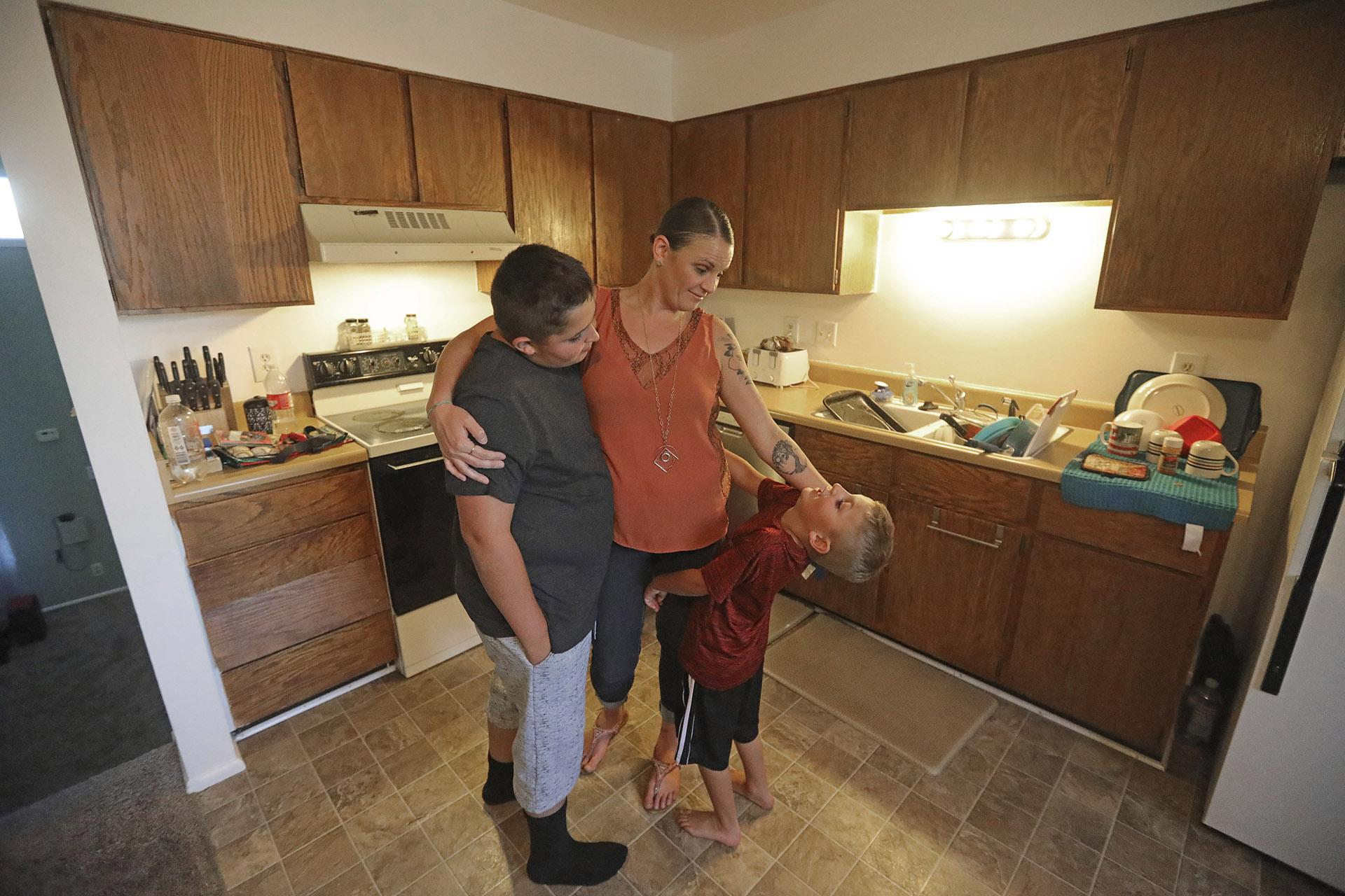 Misty Dotson hugs her son's at their home Tuesday, Aug. 20, 2019, in Murray, Utah. Dotson is a 33-year-old single mother of two boys, ages 12 and 6, who goes to Planned Parenthood for care through the Title X program. (AP Photo / Rick Bowmer)